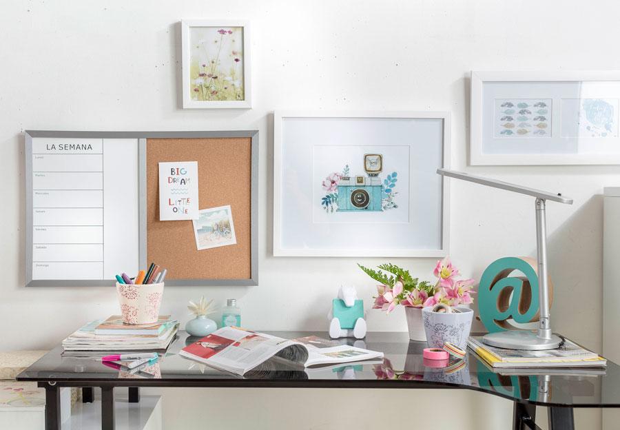 Escritorio de vidrio, decorado en colores celestes y rosas, con libros y revistas, flores y una lámpara de escritorio.
