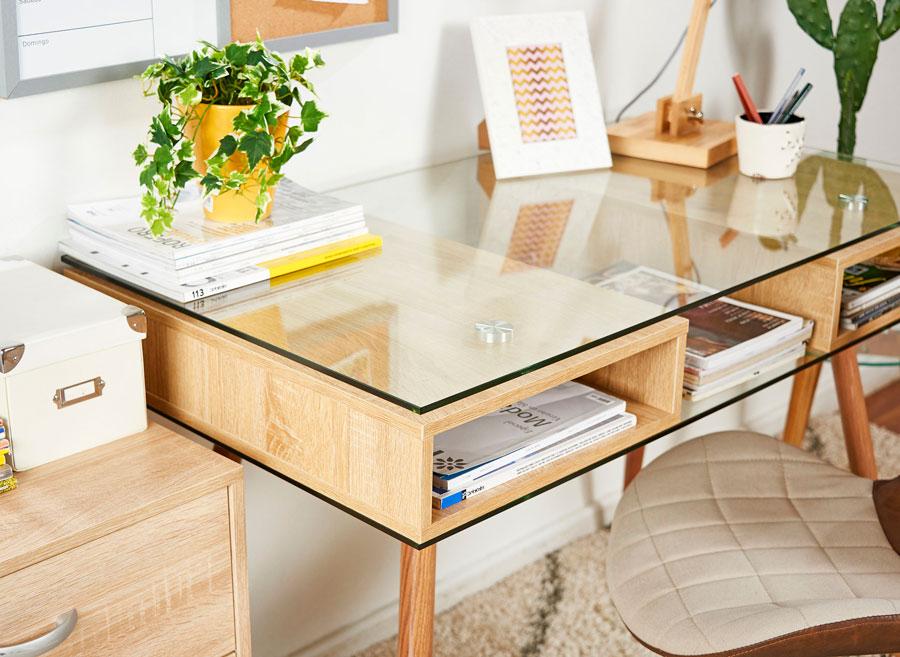Detalle de esritorio de madera natural y vidrio, ordenado y con una planta verde