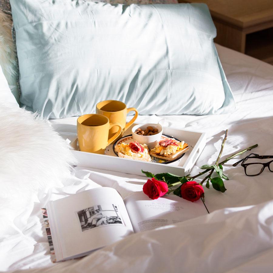 Cama con desayuno en bandeja, libro y rosas