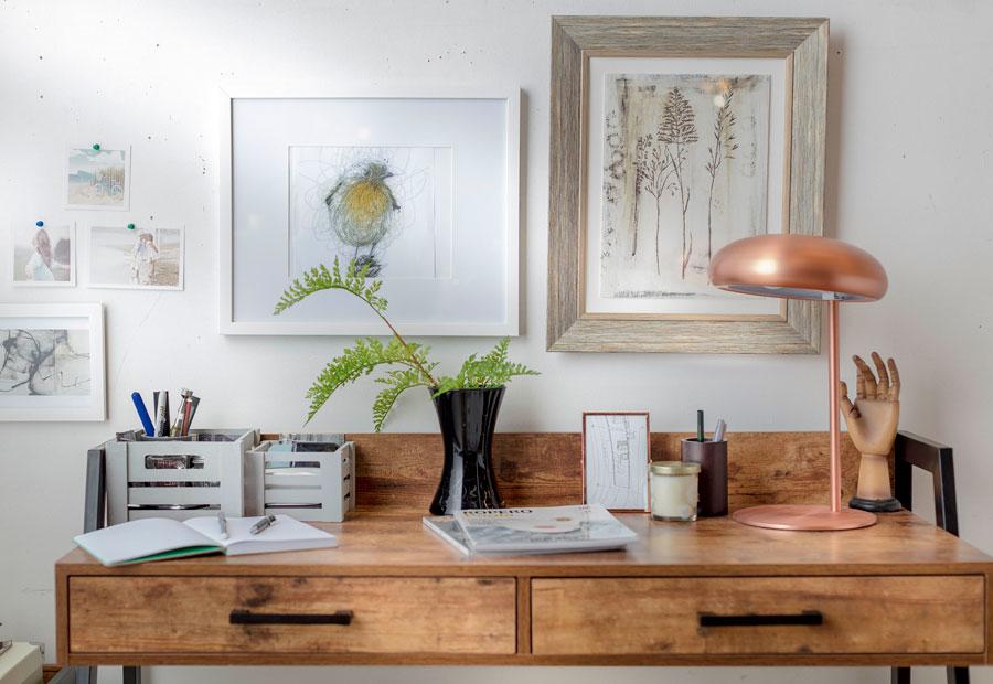 Vista frontal de escritorio de madera estilo industrial, con una lámpara de cobre y decorado con un estilo masculino, con cajas organizadoras, portalápices y un jarrón negro con hojas verdes